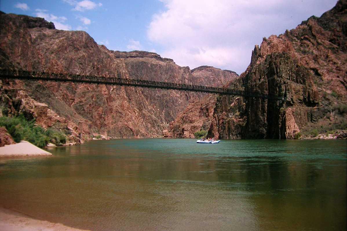 Colorado River, Black suspension bridge and raft from boat ...